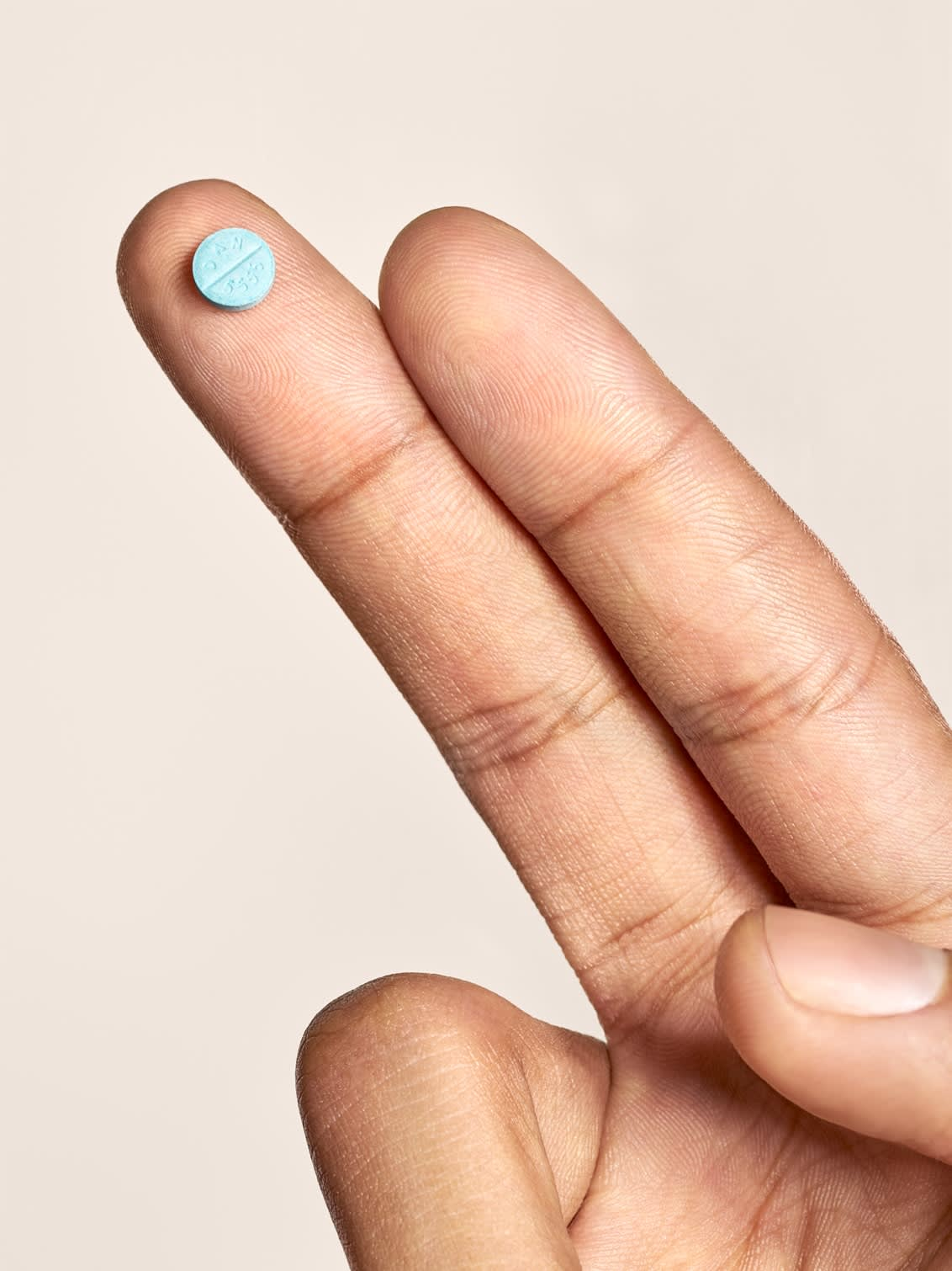 A man holding a small beta blocker pill