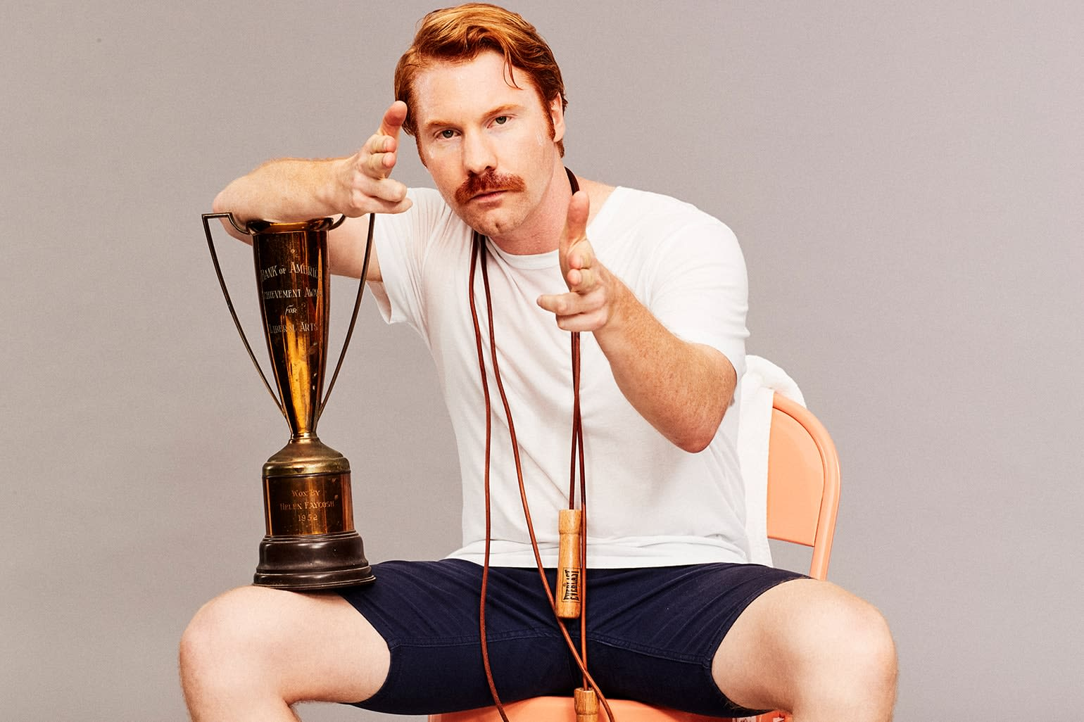 Mustached man in gym shorts - accompanied by a small trophy and exercise rope - giving you finger guns