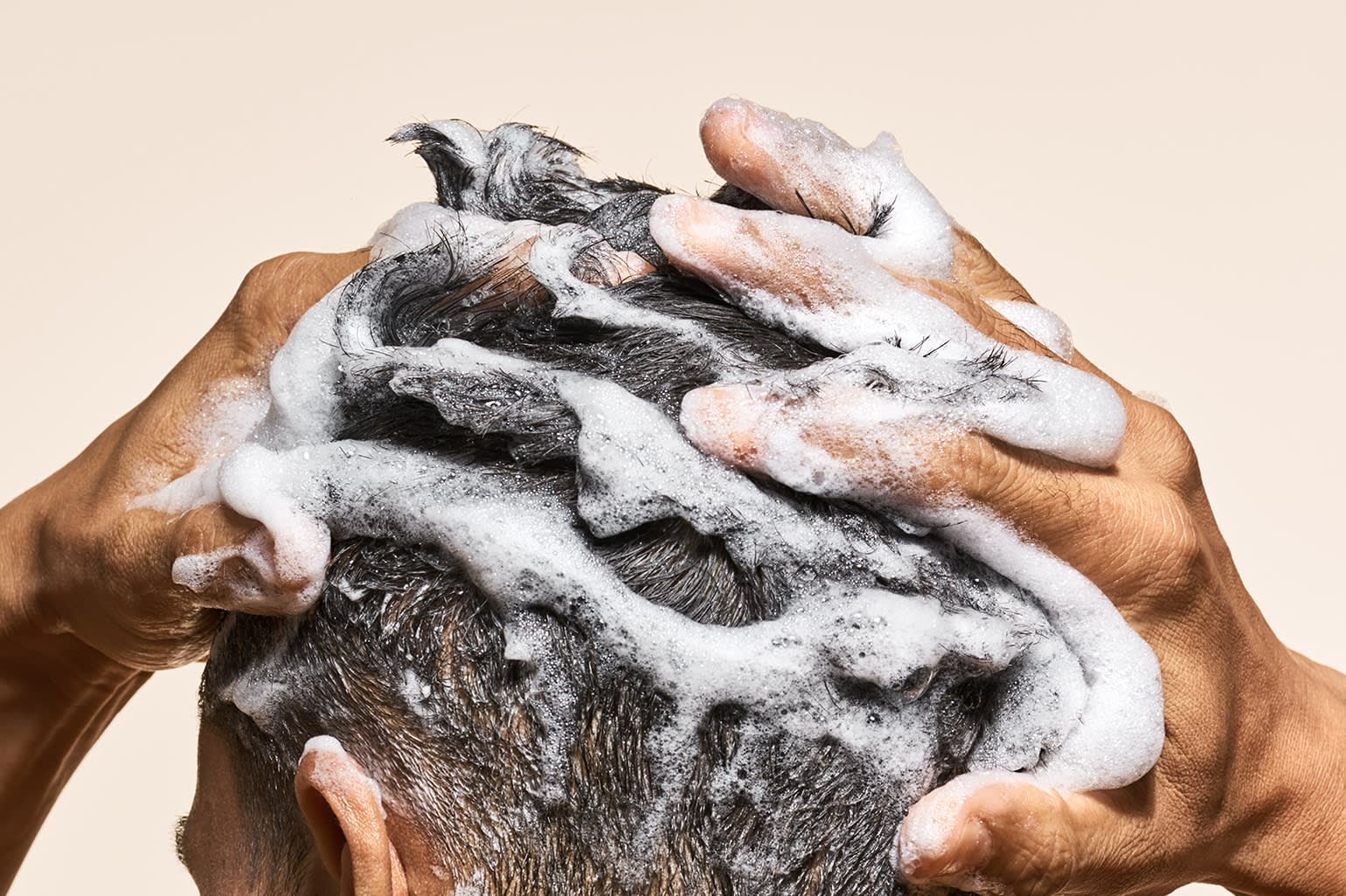 Hands lather shampoo into a man's hair