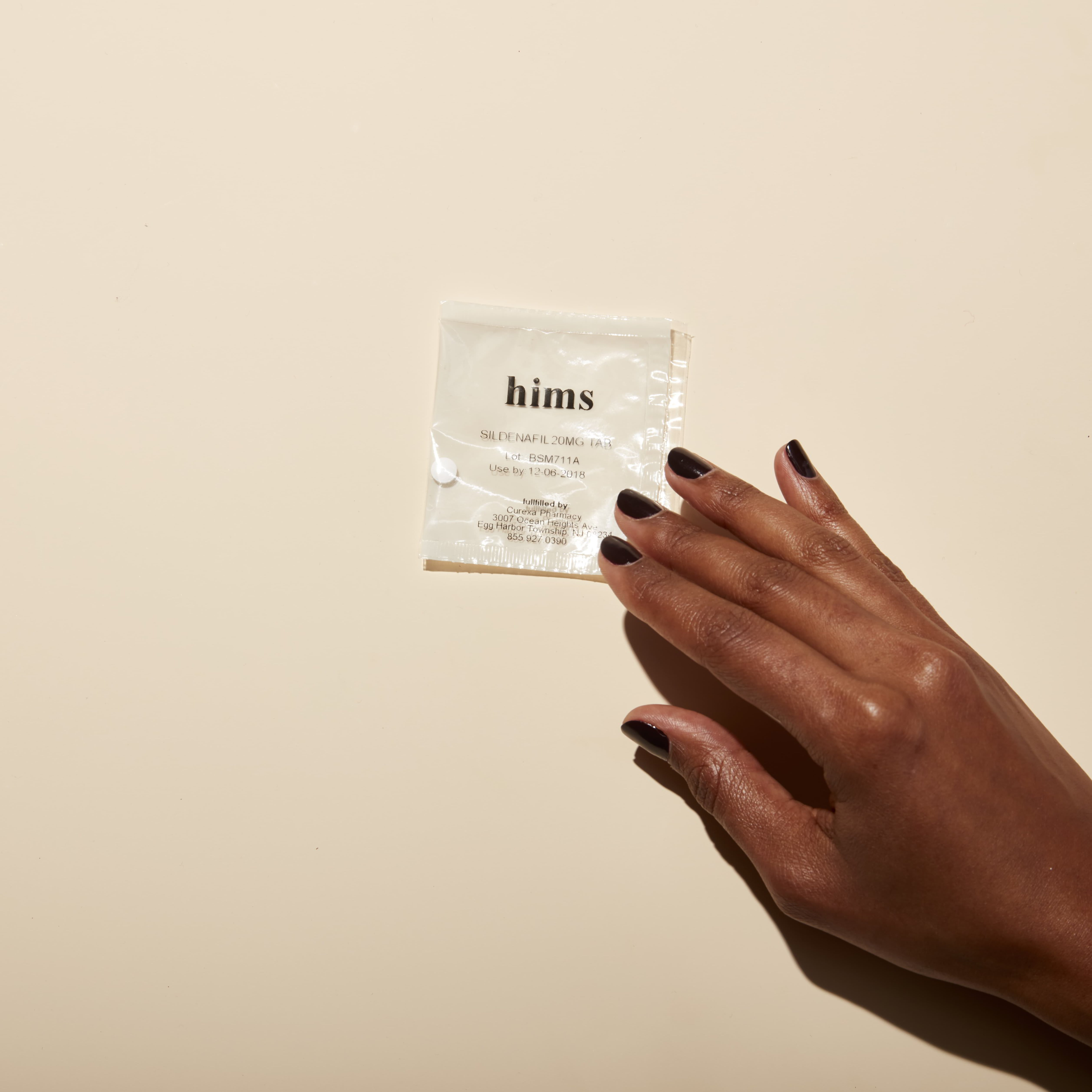 A hand holding a package of Hims Sildenafil medication