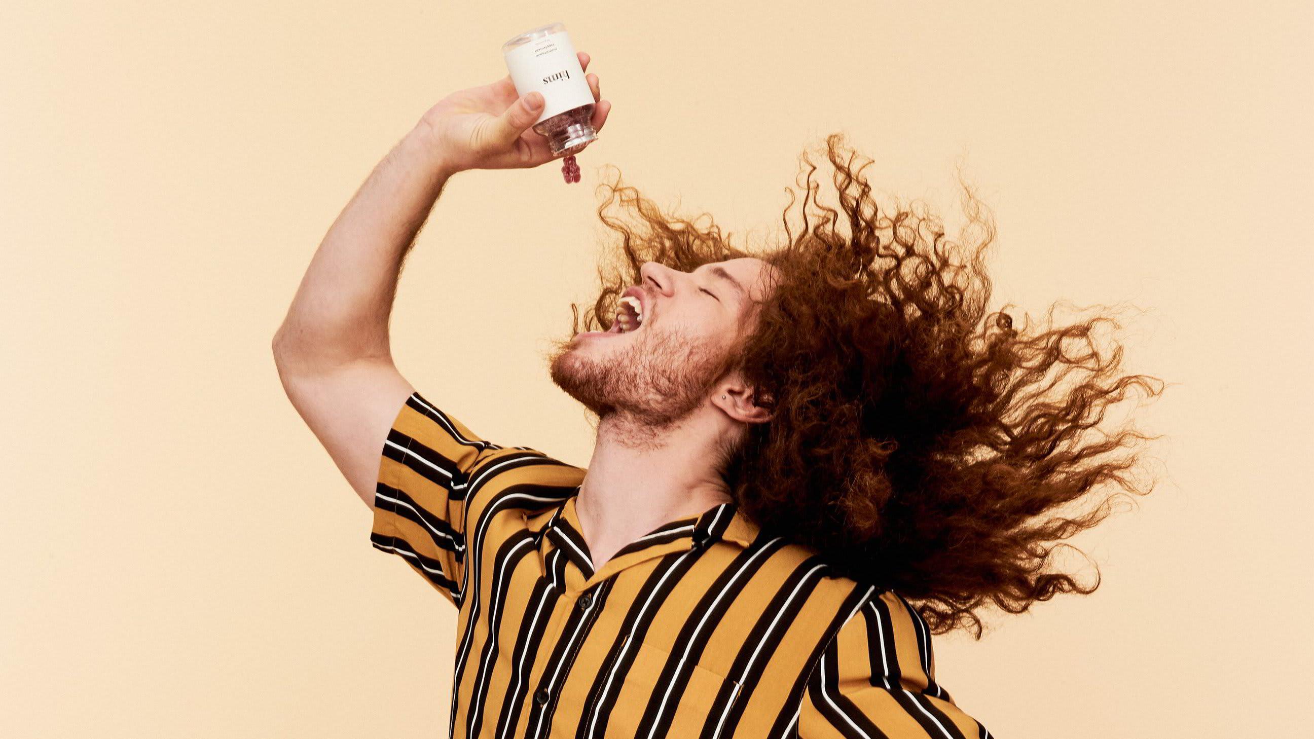 A young man with long hair dramatically eating a Hims Hair vitamin