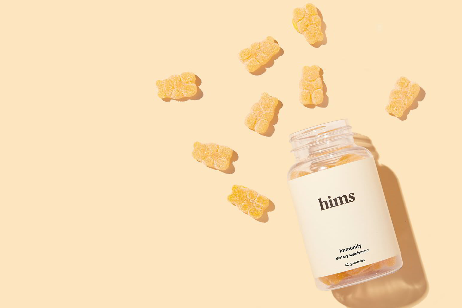 A bottle of Hims Immunity Vitamins surrounded by bear-shaped vitamins