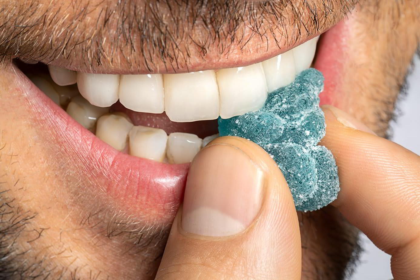 A man bites into a blue gummy