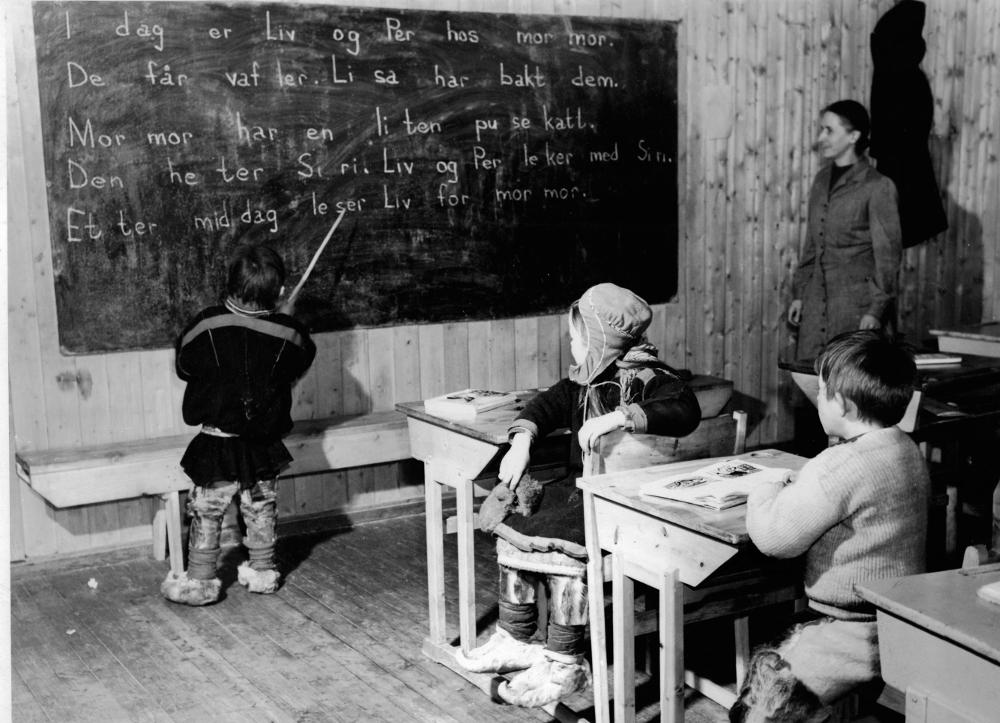 Klasserom fra 1950-tallet, elever kledd i samekofter. Undervisning i norsk, en elev er tatt opp og leser norske setninger på tavla. Lærer følger med fra sidelinja. Foto.