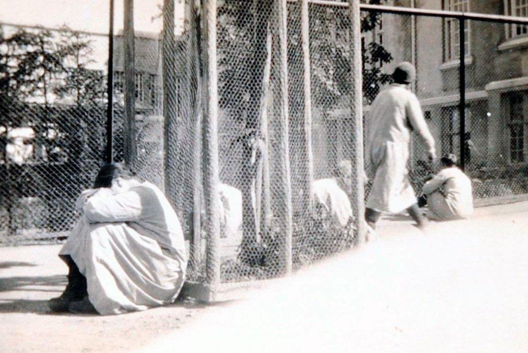 Pasienter på psykiatrisk sykehus i luftegård, de fleste sitter på bakken og ser nedtrykte ut. Omgitt av nettinggjerde. Foto fra 1930-årene.