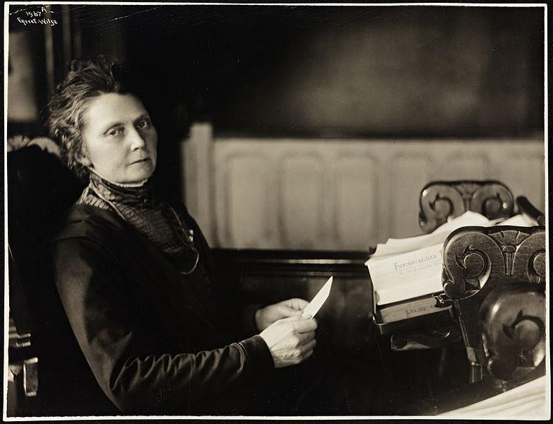 Anna Rogstad, første kvinne på Stortinget, sitter på stortingsbenk med sakspapirer foran seg. Foto.