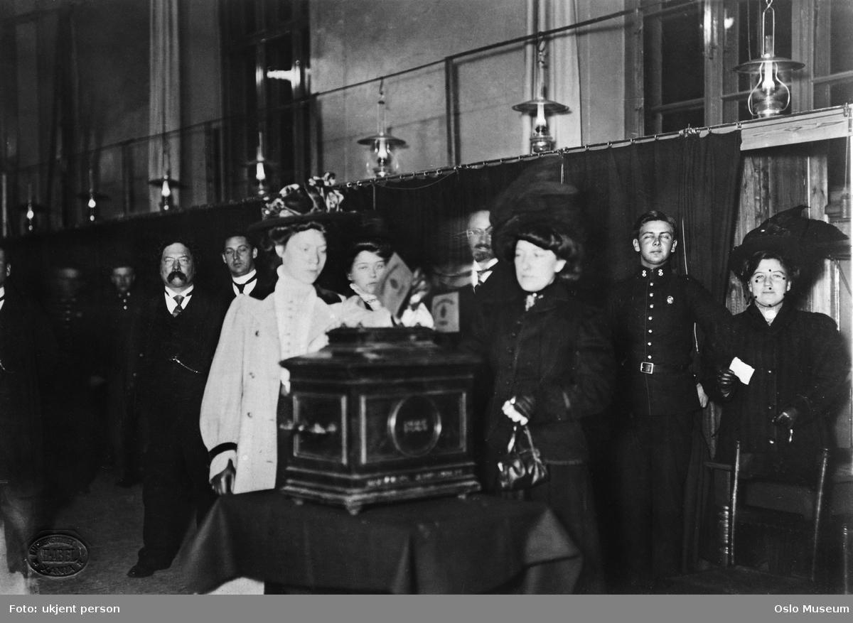 Foto fra 1910, viser valglokale der en kvinne legger stemme sin i urnen. Flere funksjonærer oppstilt i bakgrunnen.
