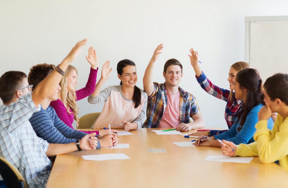 Illustrasjonsfoto fra klasserom. En gruppe ungdommer sitter rundt et bord og rekker opp hendene.
