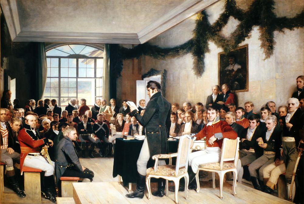 Maleri av representantene som var på Eidsvoll i 1814. De sitter i møtesalen, tett i tett. I forgrunnen er to representanter plassert ved et bord; den ene står med ryggen mot oss og leser opp loven, den andre sitter og ser mot oss.
