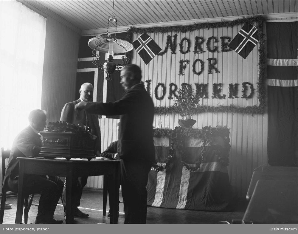 Foto fra valglokale i 1905. En mann putter stemmen sin i urnen mens to funksjonærer ser på. På veggen bak henger store flagg, kranser av løv og mottoet «Norge for nordmenn» med store bokstaver.