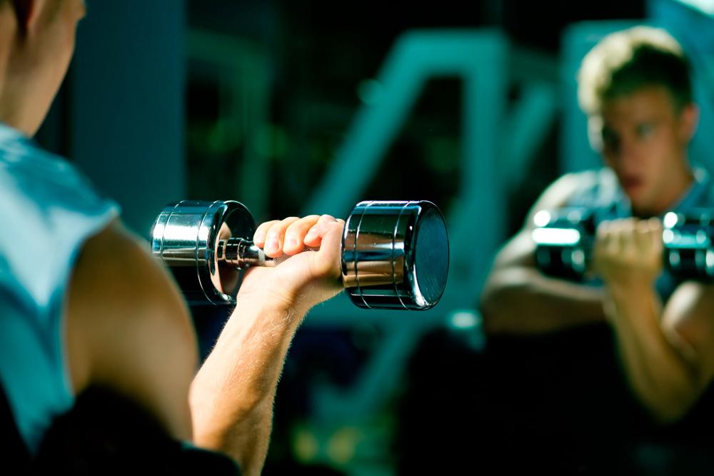Illustrasjonsfoto fra helsestudio, nærblde av gutt som trener vekter mens han ser seg i speilet.