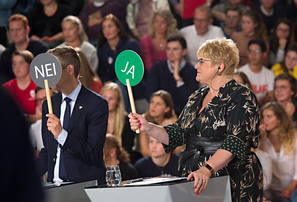 Foto fra TV-debatt med partiledere. Knut Arild Hareide fra Kristelig Folkeparti og Trine Skei Grande fra Venstre holder opp avstemmingsskilt med «JA» og «NEI».