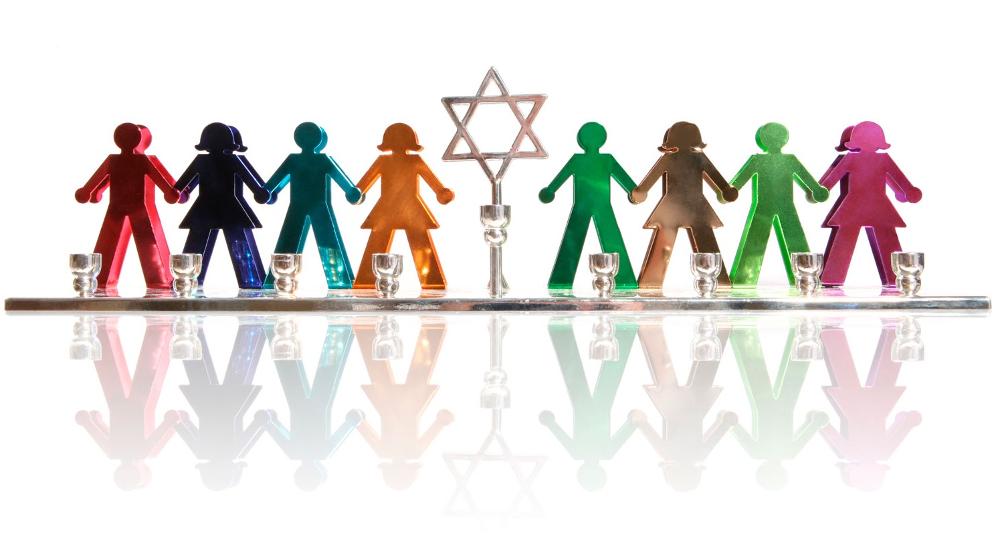 Illustrasjonsfoto av figurer på rekke og rad – menn og kvinner i forskjellige farger. De ligner på sånne remser man klipper ut i papir. I midten en jødestjerne som står på en stang. Illustrasjonen skal symbolisere det jødiske folket eller den jødiske kulturen.
