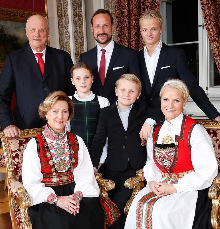 Portrettfoto av kongefamilien: Sonja og Harald, Haakon Magnus og Mette Marit, Ingrid Alexandra, Sverre Magnus og Marius. De er samlet på Skaugum til jul; Sonja og Mette Marit har bunad.