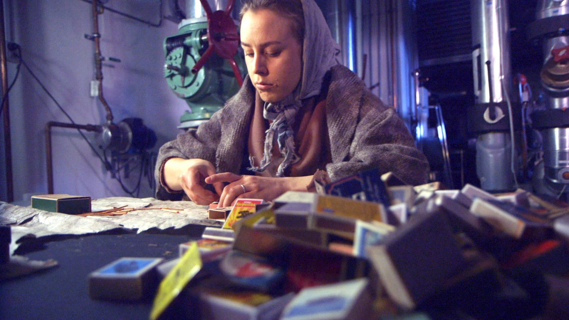 Skjermdump fra NRKs dramatisering av fyrstikkarbeiderstreiken. Programlederen utkledd som arbeider på 1800-tallet sitter og pakker fyrstikker i eske. Omgivelser fra gammel fabrikk.