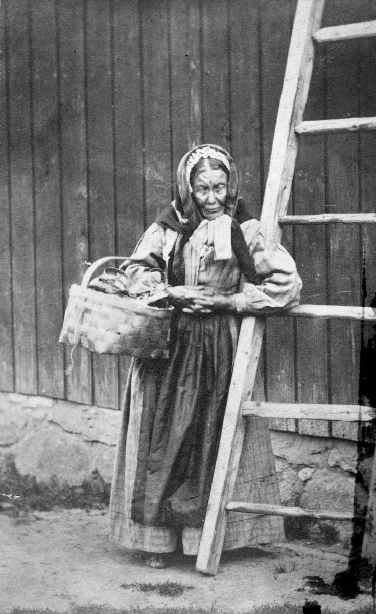 Foto fra 1800-tallet som viser en gammel, fattig dame på landsbygda. Hun holder en kurv i hånden med småting som hun selger.