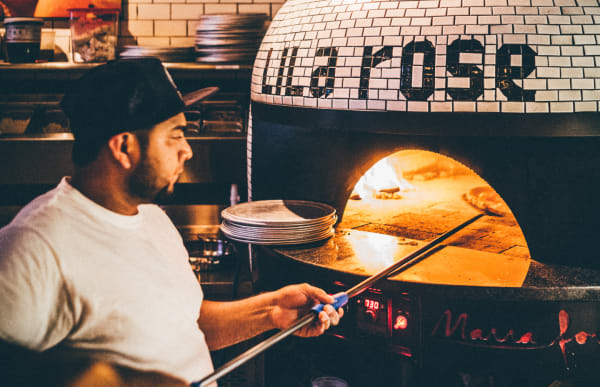 Team member cooking pizza in the custom oven, names 'Lila Rose'