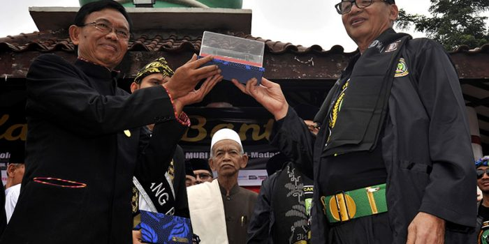 Gubernur Banten Wahidin Halim (kanan) menyerahkan miniatur golok Ciomas kepada koordinator Museum Rekor Indonesia (MURI) Sugi Raharjo (kiri) saat Pertunjukan Debus Terbanyak di Alun-alun Serang, Banten, Minggu (19/11). MURI mencatat atraksi debus yang diikuti 3 ribu peserta itu merupakan rekor atraksi debus terbanyak. ANTARA FOTO/Asep Fathulrahman/ama/17