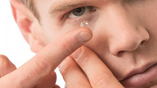 Mann setzt sich Kontaktlinsen ein.