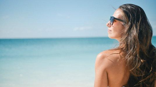 Frau ist entspannt mit Sonnenbrille am Strand.
