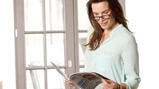 Frau mit Lesebrille, die in Zeitschrift liest.