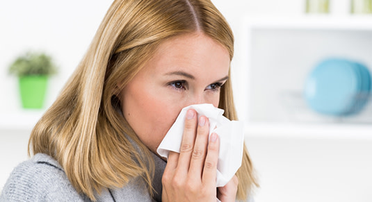 Frau beim Naseputzen