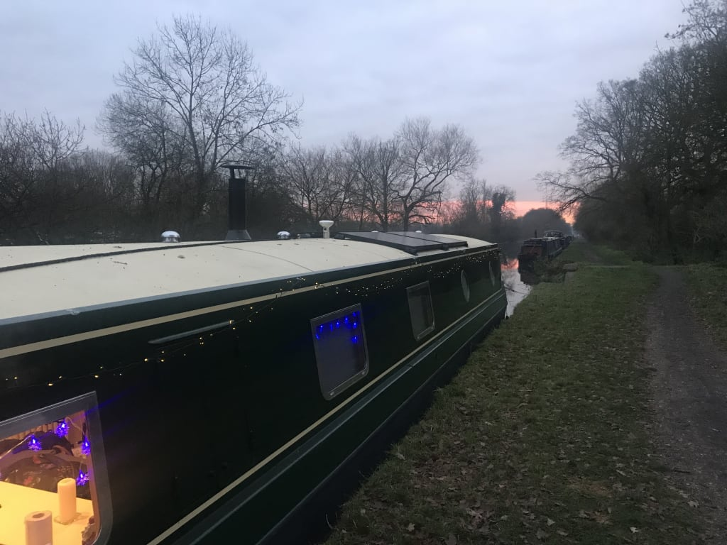 Widebeam canal boat with Christmas lights visible on the hull