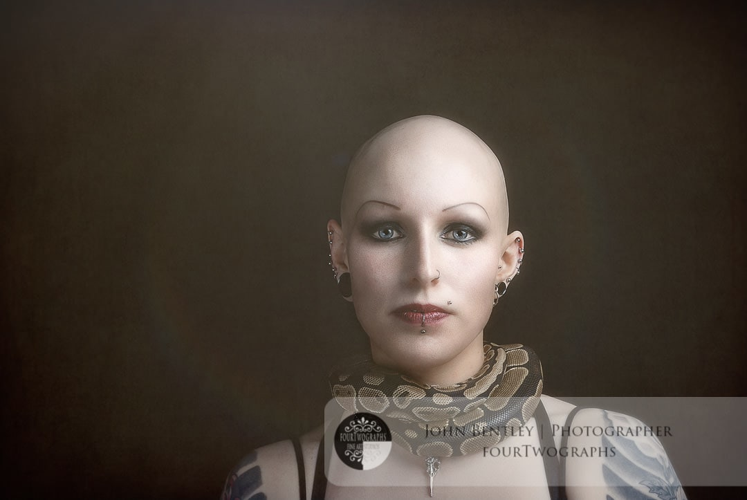 Young lady with bald head and royal python around her neck