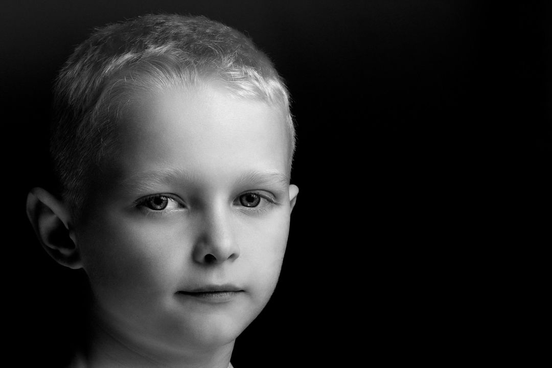 young boy photographed on black background.