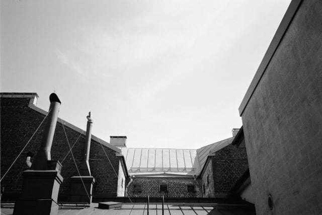 A view upwards onto rooftops. Chimneys, maintenance ladders, and ventilation shafts line the tops. The light is coming from a right angle beyond the frame, casting hard shadows where they appear.