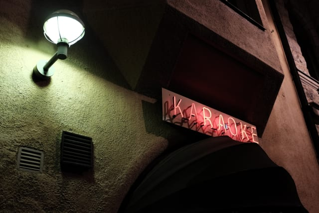 The red neon sign of a Karaoke bar, by the pale green glow of a street lamp.