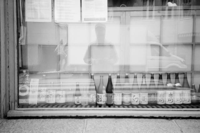 A shop window, lined with bottles. The photographer is reflected with their hands on the camera a bit above waist level. A truck with people loading it is reflected behind them.