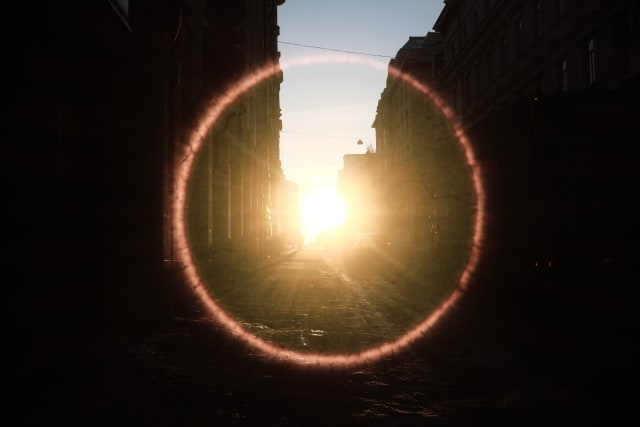 A mostly shaded city on the sides and bottom. The sun is intensely shining in the middle, with a bright red halo that almost sears the image.