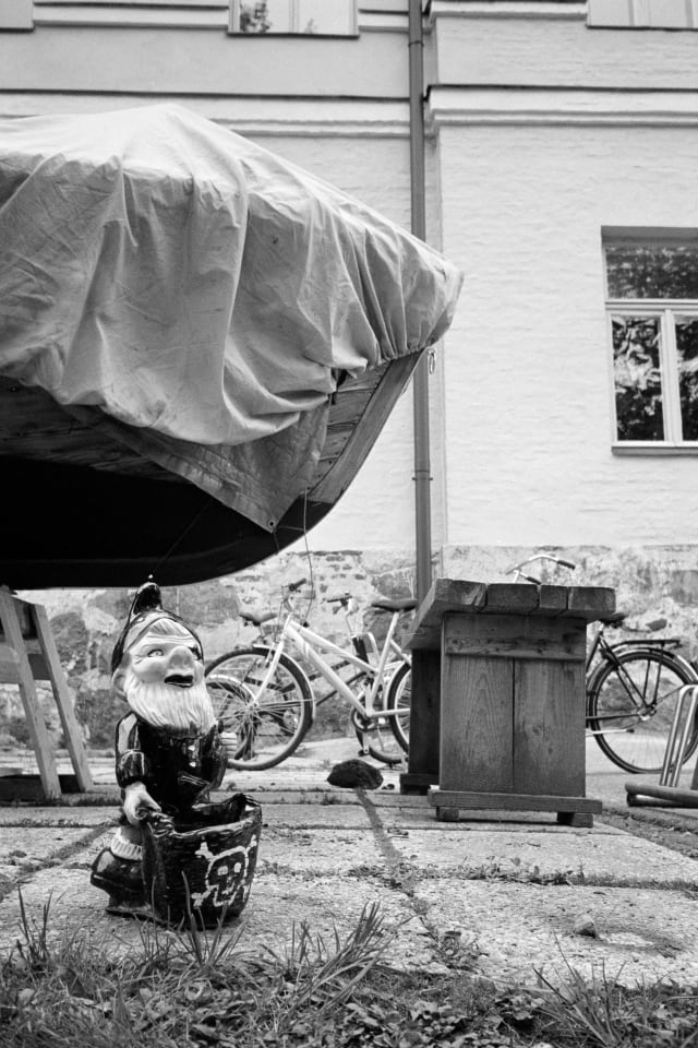 A garden gnome viewed from the ground level, with a skull and bones bucket in front of them. They have a smirk and some cool lipstick. Behind them, there are bikes, a small boat under a tarp, and an old building.