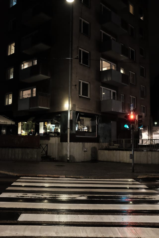 A street corner, with a pedestrian crossing leading up to it. Surfaces reflect street lights after the rain. A person is sitting at a bar, while above it apartment lights are on.