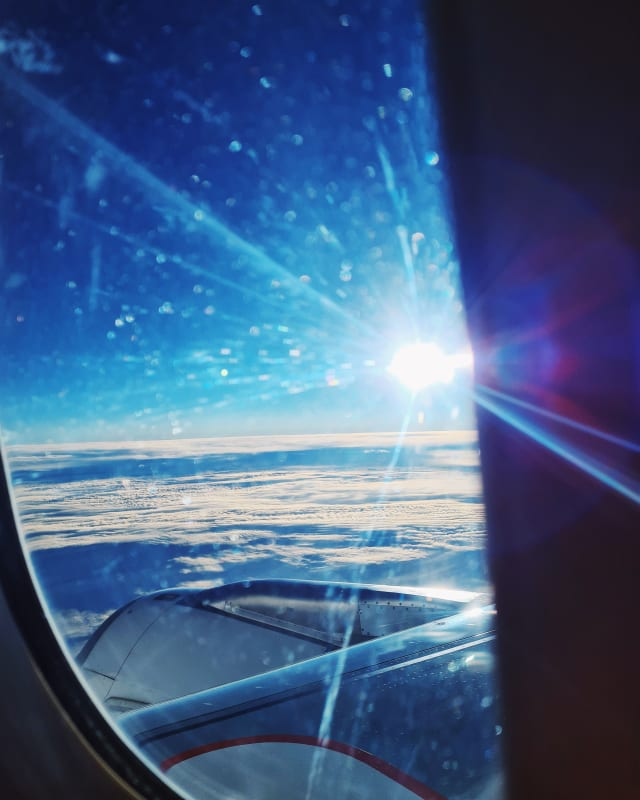 An airplane window. The sun, or maybe a reflection of it, shines prominently over a sea of clouds, flaring across the frame.