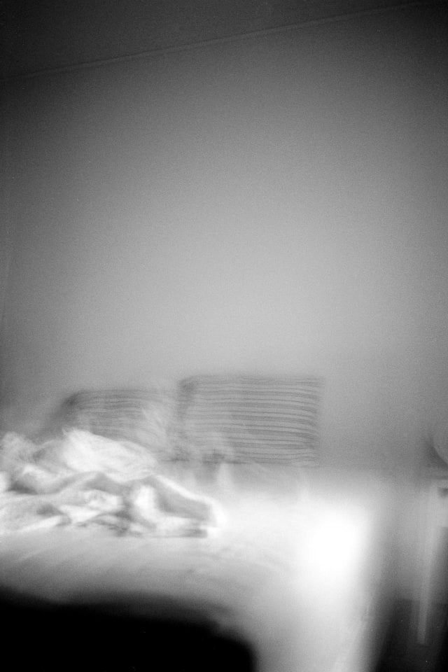A blurry and shaky view of a bed or bedroom. Shadows line the edges of the frame. On the bed, two pillows are standing haphazardly, and a blanket is draped at an angle.