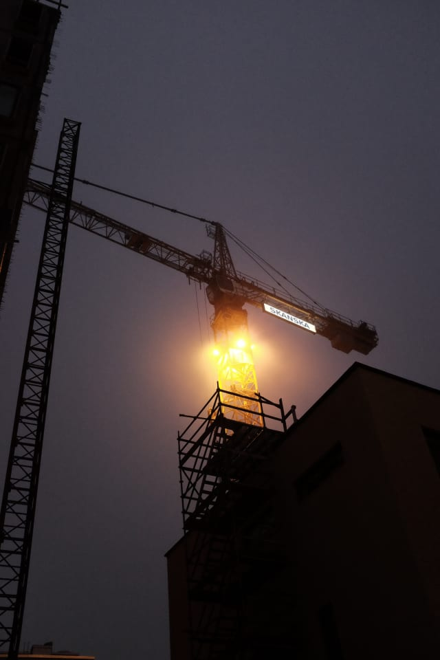 A crane standing in a dark sky, between shaded buildings.