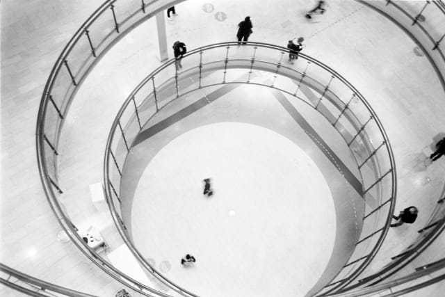 A top-down view of three floors of a shopping mall, through a circular opening. People are standing or walking around each floor. The circles of each floor are merging into each other, leading to a spiral-like effect.