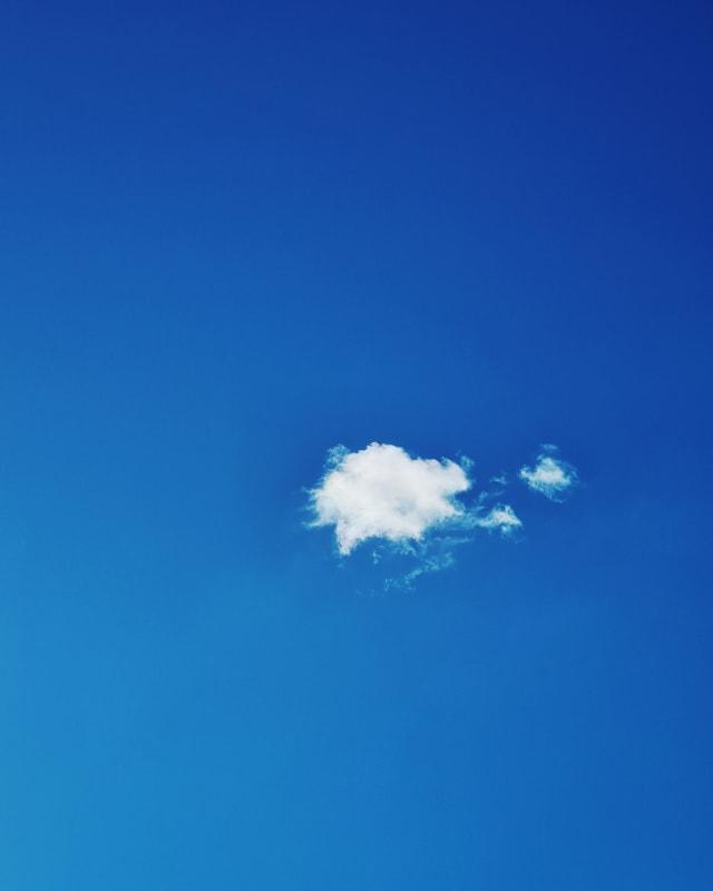 A single cloud in a deep blue sky.
