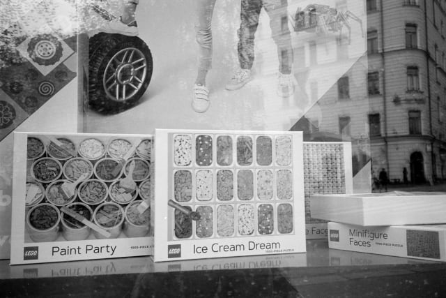 """A shop window, with multiple reflections of the city on it. Boxes of LEGO line the display, titled """"Paint Party"""", """"Ice Cream Dream"""" and """"Minifigure Faces""""."""