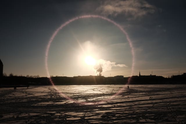 A landscape over Helsinki. The icy sea stretches over the bottom of the frame, leading to a shaded outline in the distance. The sun is in the middle casting a glare on the lens and landscape. Figures of people dot the ice.