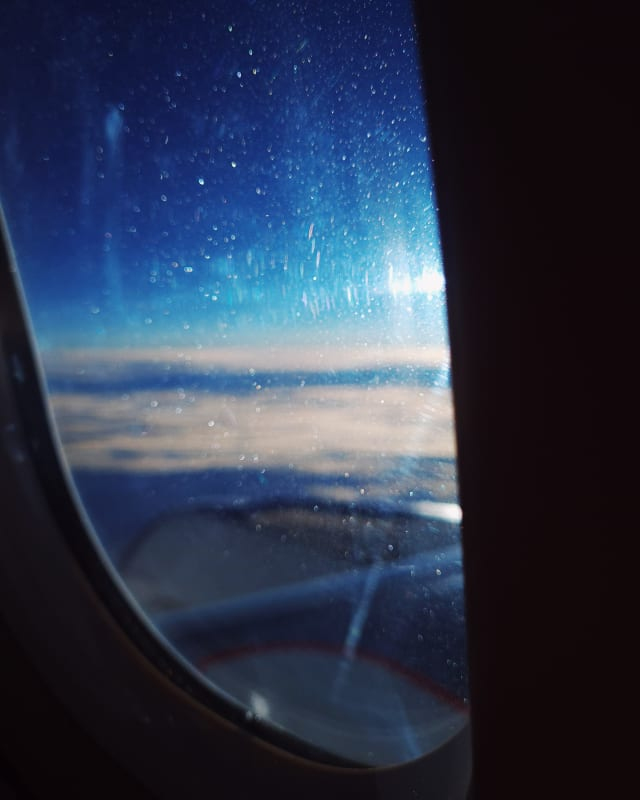 An airplane window, slightly blurry, with mostly the details and scratches on it being distinct. A reflection of the sun flares into rays near the edge of the window.