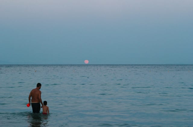 An adult and a child standing in shallow waters, in front of a pale red moon.