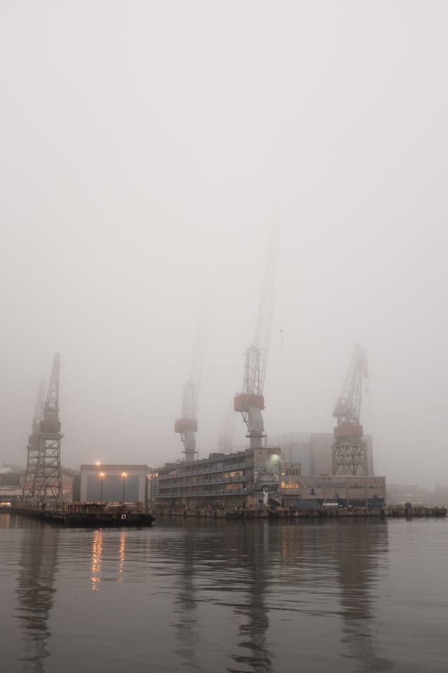 A gray sea in the foreground, with a dockyard in the background. Cranes stand tall and get lost in the fog.