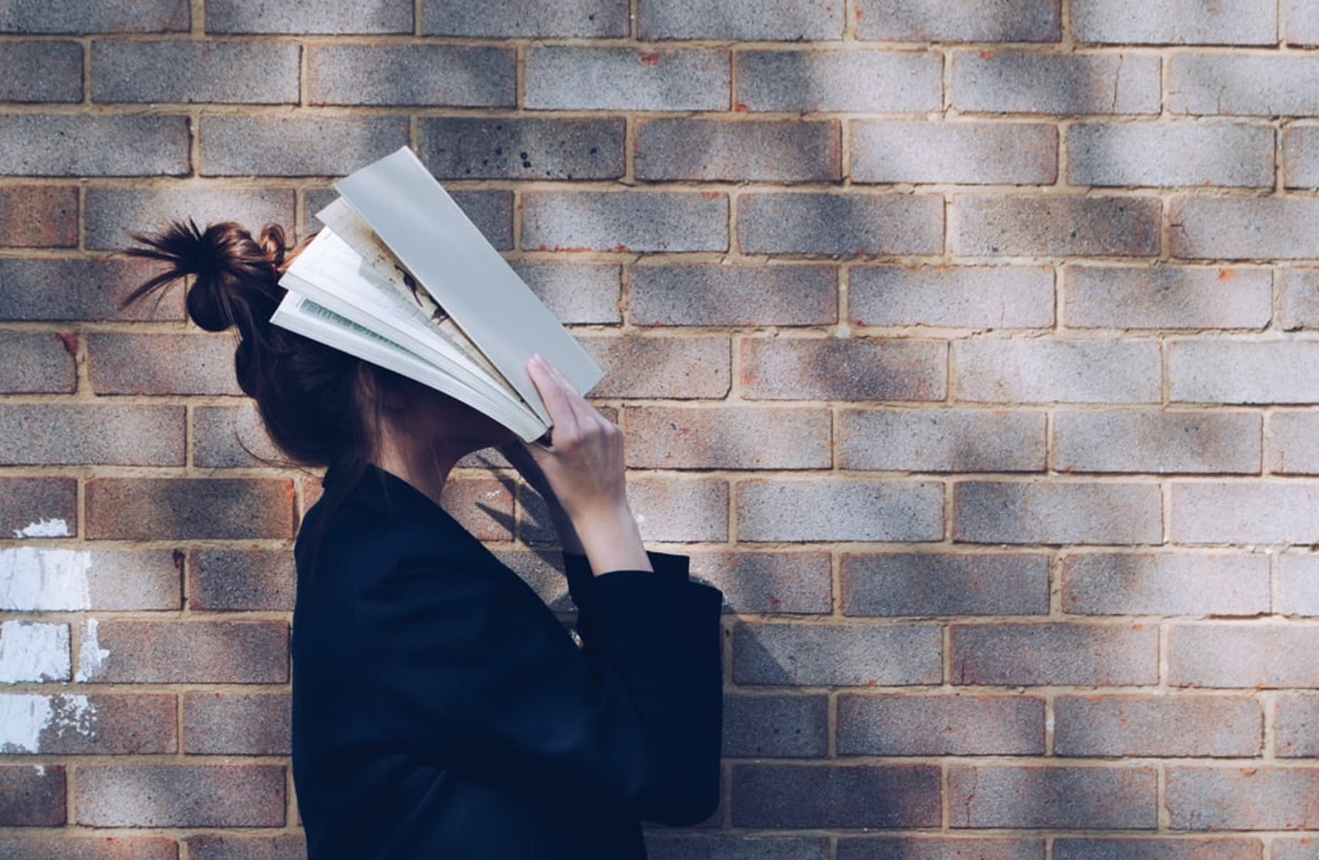 picture of lady covering face with a text book - suggesting she is stressed