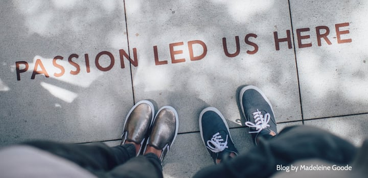 Image showing the feet of two young people in trainers standing on asphalt and the words 'Passion led us here' printed on the road surface