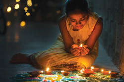 Girl decorating Rangoli with oil lamps