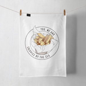 A Chippies by the sea tea towel hanging on a line