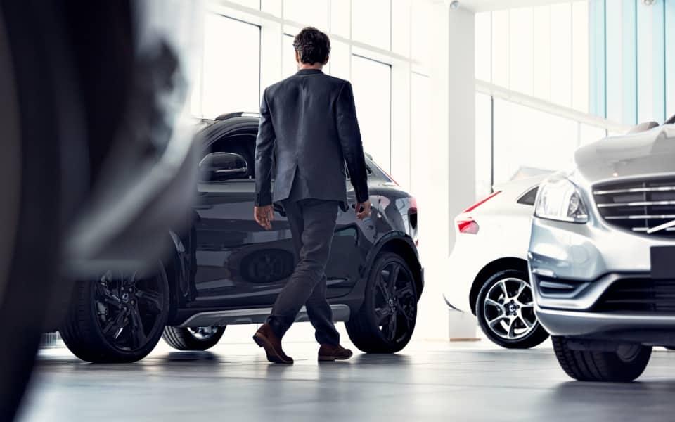 En mann I dress går å ser på ulike bruktbiler.